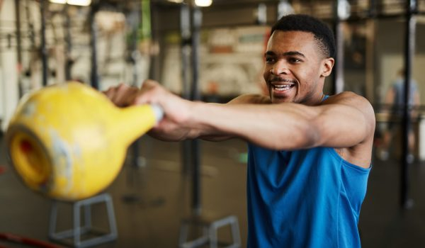Waist up portrait of strong African-American man swinging kettlebell during cross workout in modern gym, copy space
